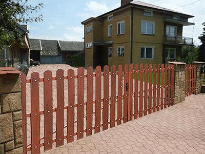 Zastosowanie sztachety plastikowe jako element bramy. Obraz za https://ogrodzeniaplastikowe.pl/galeria-ogrodzen-exclusive/